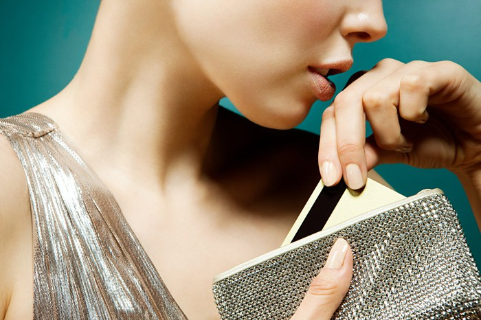 A woman takes a credit card out of a sparkly luxury wallet.
