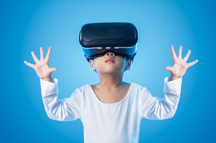A little boy with a VR headset on in front of a blue screen.