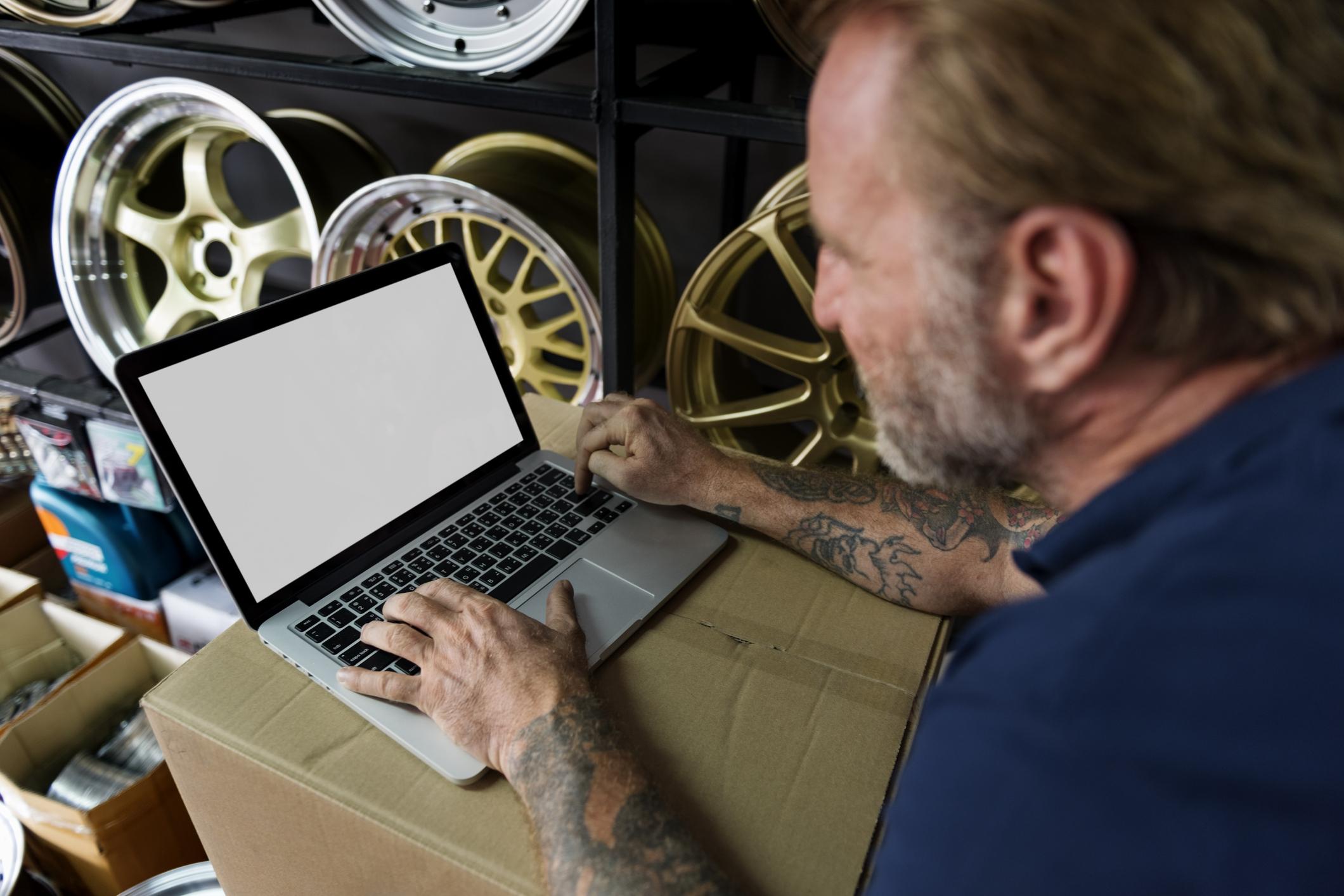 Auto retailer shop owner on a laptop