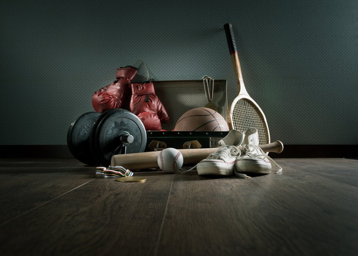 A collection of sporting goods including a baseball bat, boxing gloves, and a tennis racket