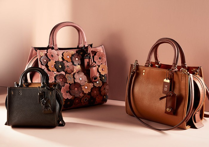 Three Coach purses, one black, one with leather flowers in various shades, and one brown.