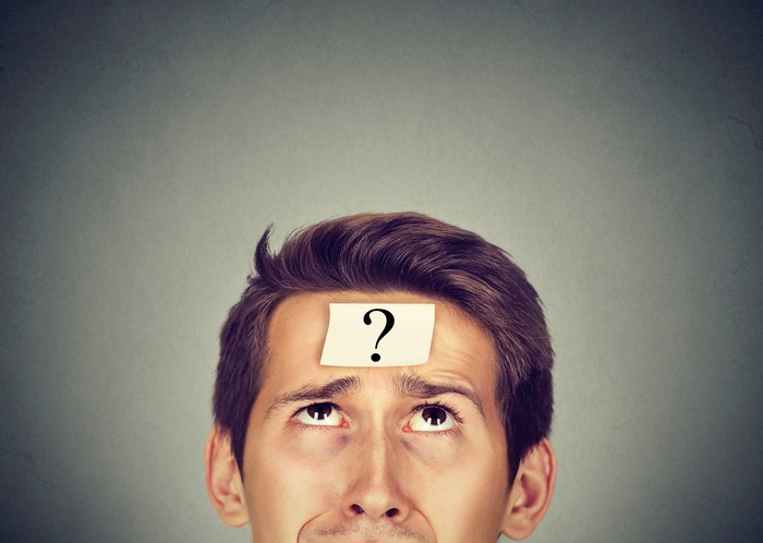 A man looks up at a sticky note with a question mark located on his forehead.