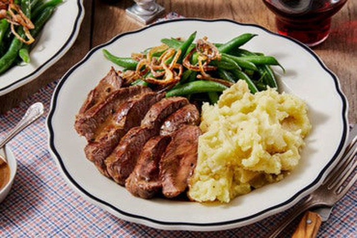 A plate of steak, mashed potatoes, and green beans