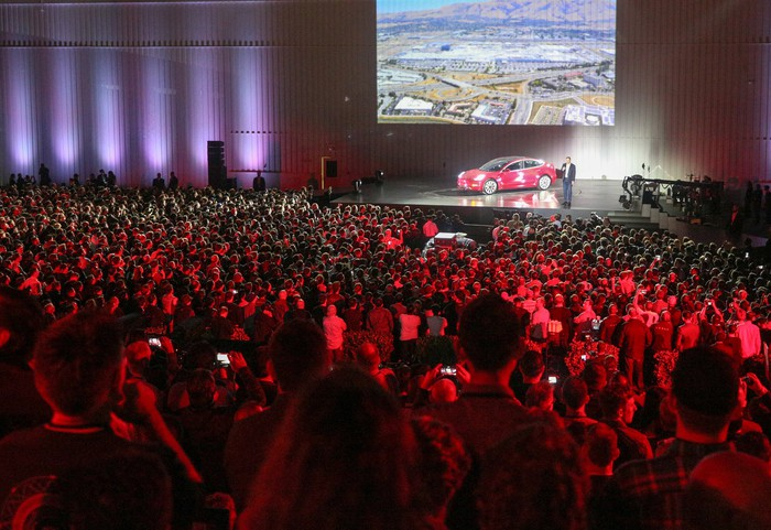 Tesla unveils the final version of its Model 3 at an event.