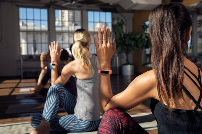 Alta HR worn by all members of a Yoga class stretching with their hands up showing off their Fitbits.