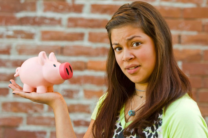 A young woman with a confused look holding a piggy bank in her right hand.