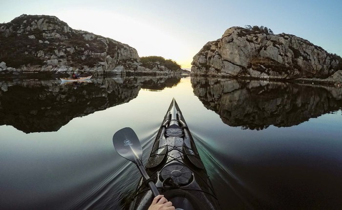 Picture from point of view of person in kayak looking at a lake smooth as glass just before sunrise and two rock islands ahead.