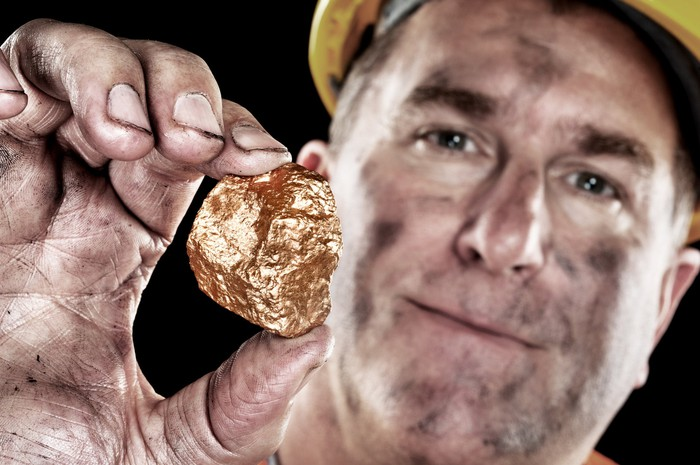 A man wearing a yellow hard hat and with a coal-darkened face, holding a gold nugget