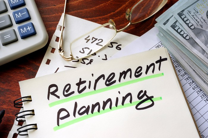 """Notebook labeled """"retirement planning"""" on desk next to calculator, glasses, and stack of money."""