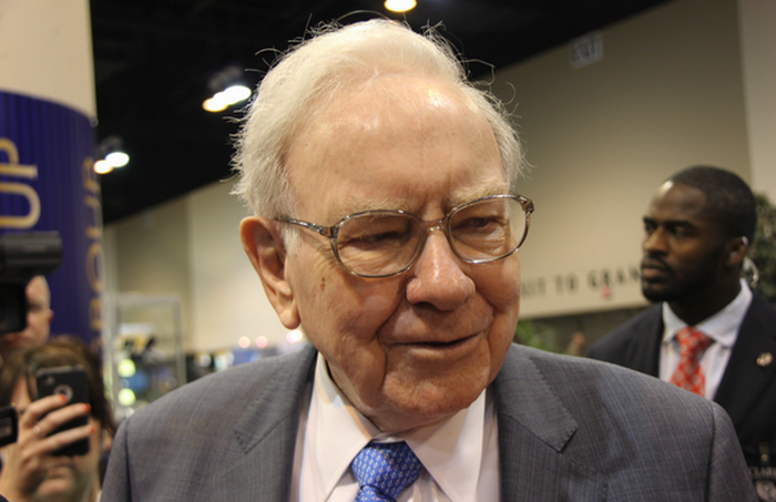 Warren Buffett speaks to someone in a crowd.