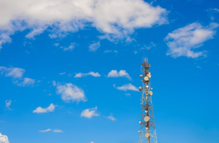 A cell phone tower, equipped with many antenna dishes, set against a partly cloudy sky.