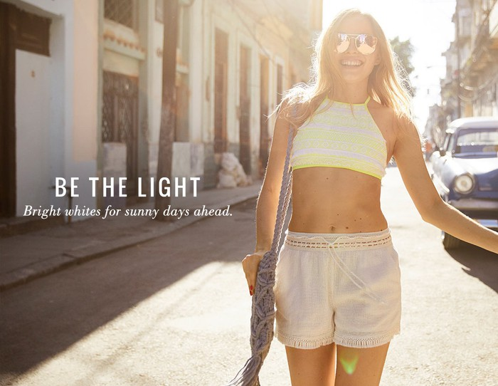 American Eagle ad featuring woman in summer clothing on a sunny street in a city.