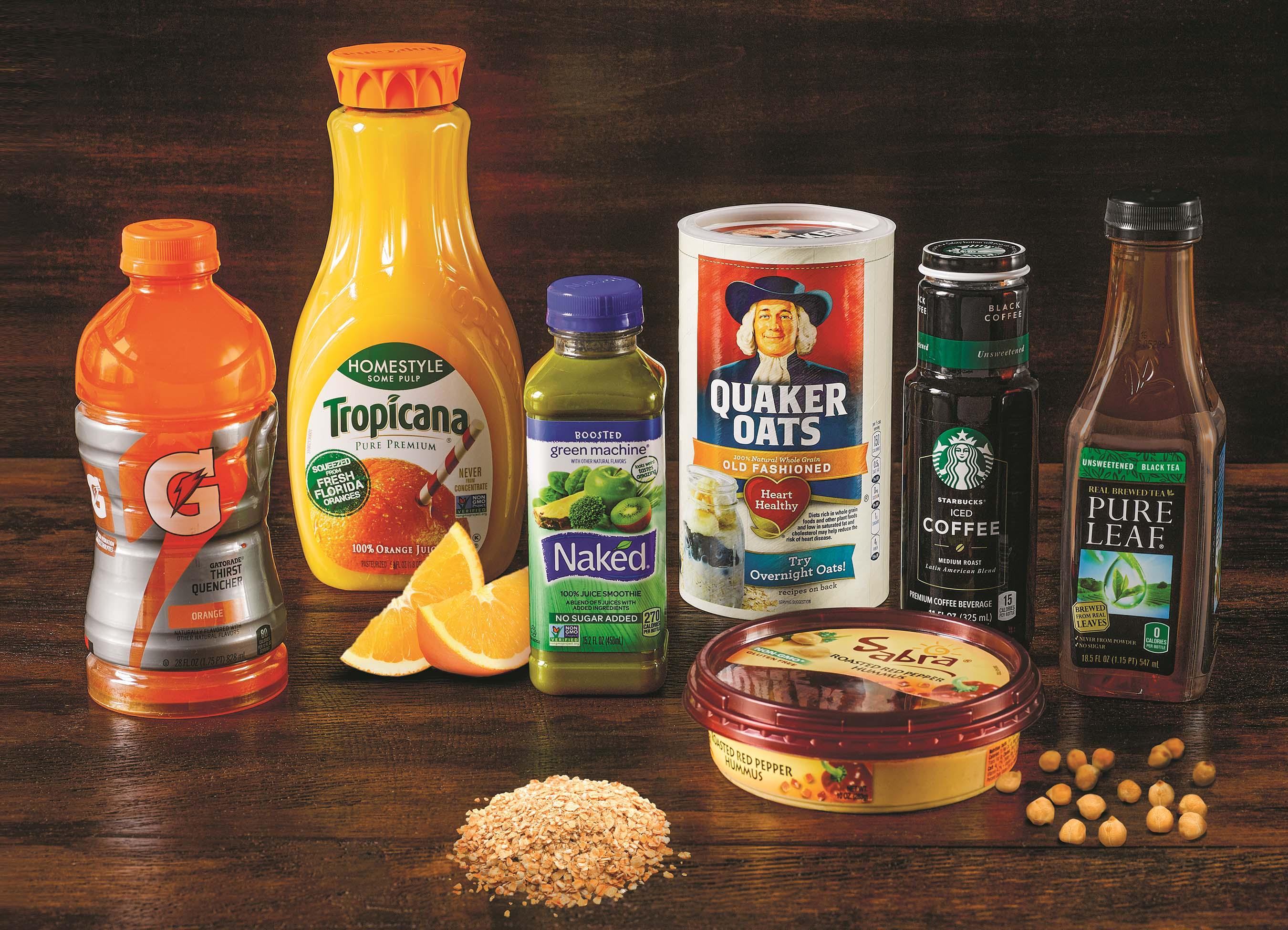 Gatorade, Tropicana juice, Naked juice, Quaker oats, Starbucks packaged coffee, Pure Leaf tea, and Sabra hummus on a table.