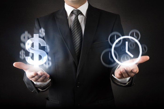 Man wearing suit holding hands out with glowing image of dollar symbols over his right hand and glowing symbols of clocks over his left hand