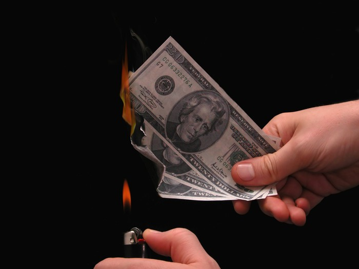 One hand is holding three twenty-dollar bills while the other hand is setting the bills on fire with a lighter.