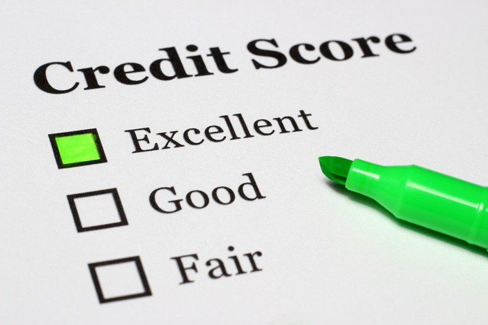 """The words """"credit score"""" printed on a paper, with """"excellent,"""" """"good,"""" and """"fair"""" below it and a green highlighter pen marking the word """"excellent"""""""