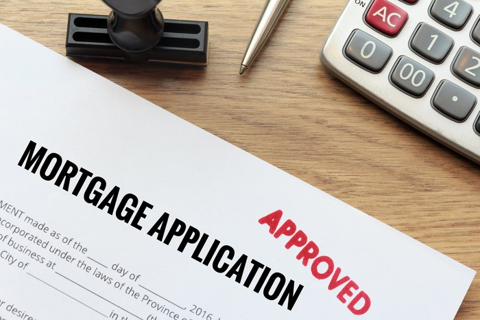 "The top of a mortgage application, stamped ""approved"" in red, next to a calculator"