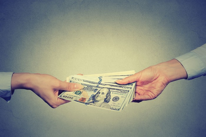 One hand passing money to another hand over a gray background.