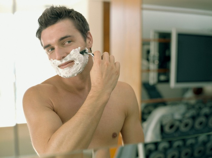 A man shaving in front of a mirror.