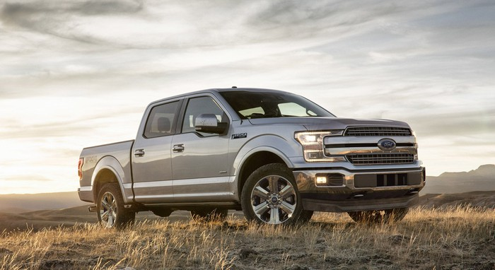 A silver 2018 Ford F-150 pickup truck, on a grassy plain.