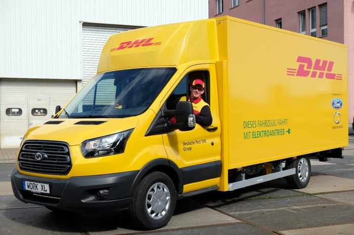 A Ford-badged electric delivery truck in yellow and red DHL livery.