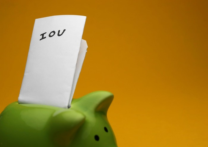 """A folded piece of paper marked """"IOU"""" protrudes from the slot of a green piggy bank."""