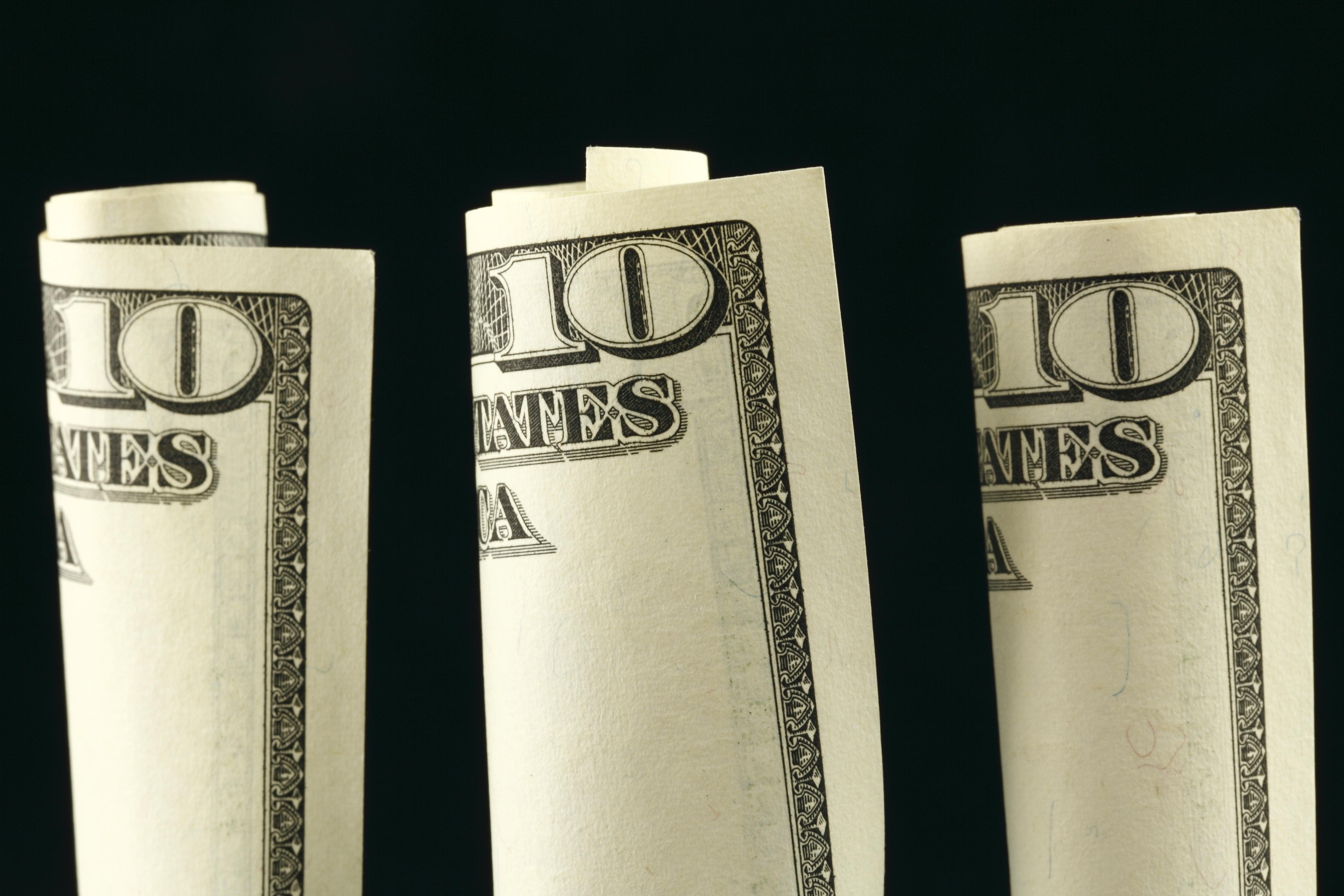 Three $10 bills rolled up