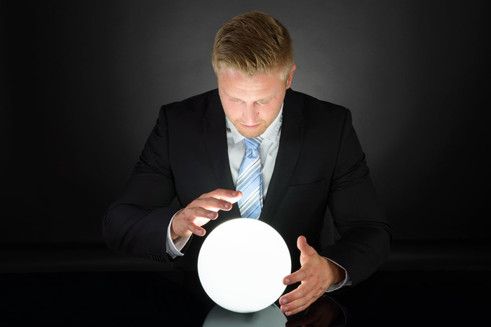 A man in a suit looking at a crystal ball.