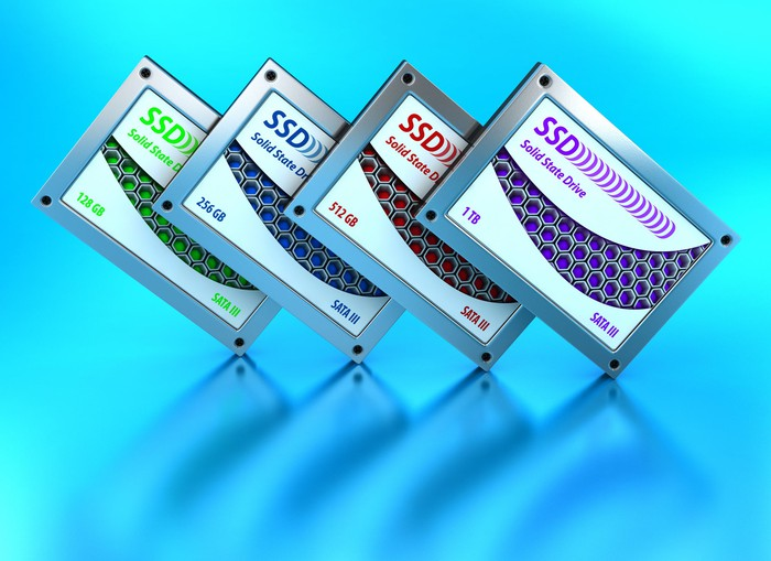 Four unbranded solid-state storage devices against a light blue backdrop.