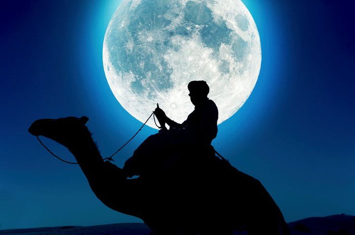 Tuareg man on camel at night with moon in background.