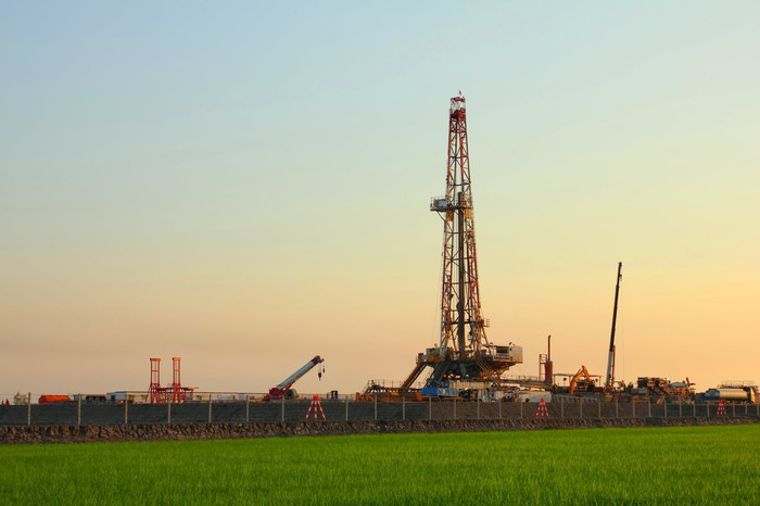 An onshore drilling rig in a green field.
