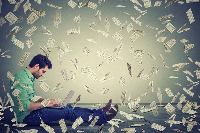 A man sitting against a wall, browsing on his laptop, as dollar bills fall around him.