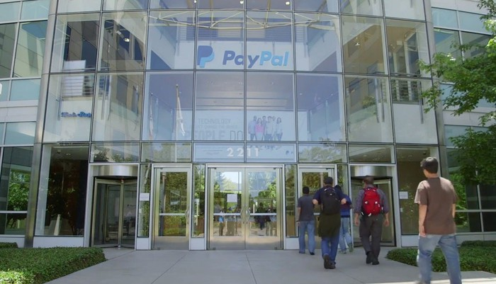 A handful of people walking into PayPal headquarters.