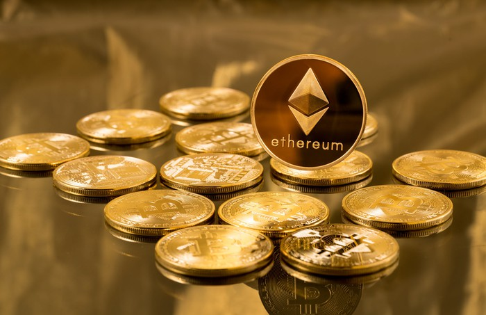 An Ethereum coin propped on several bitcoins.