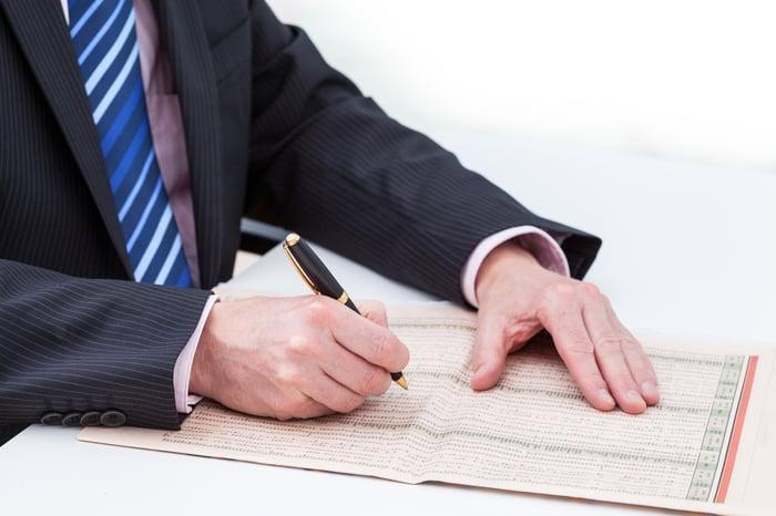 A man circling stocks in a newspaper list.