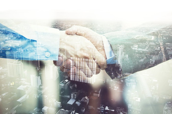 Two businessmen shaking hands superimposed over an urban setting