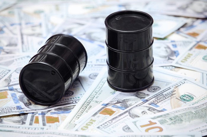 Two oil barrels on top of U.S. currency.