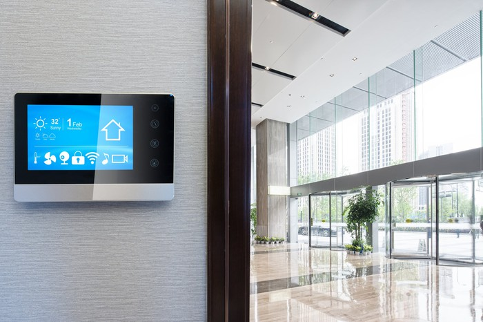 A smart home device hanging on the wall of an office lobby.