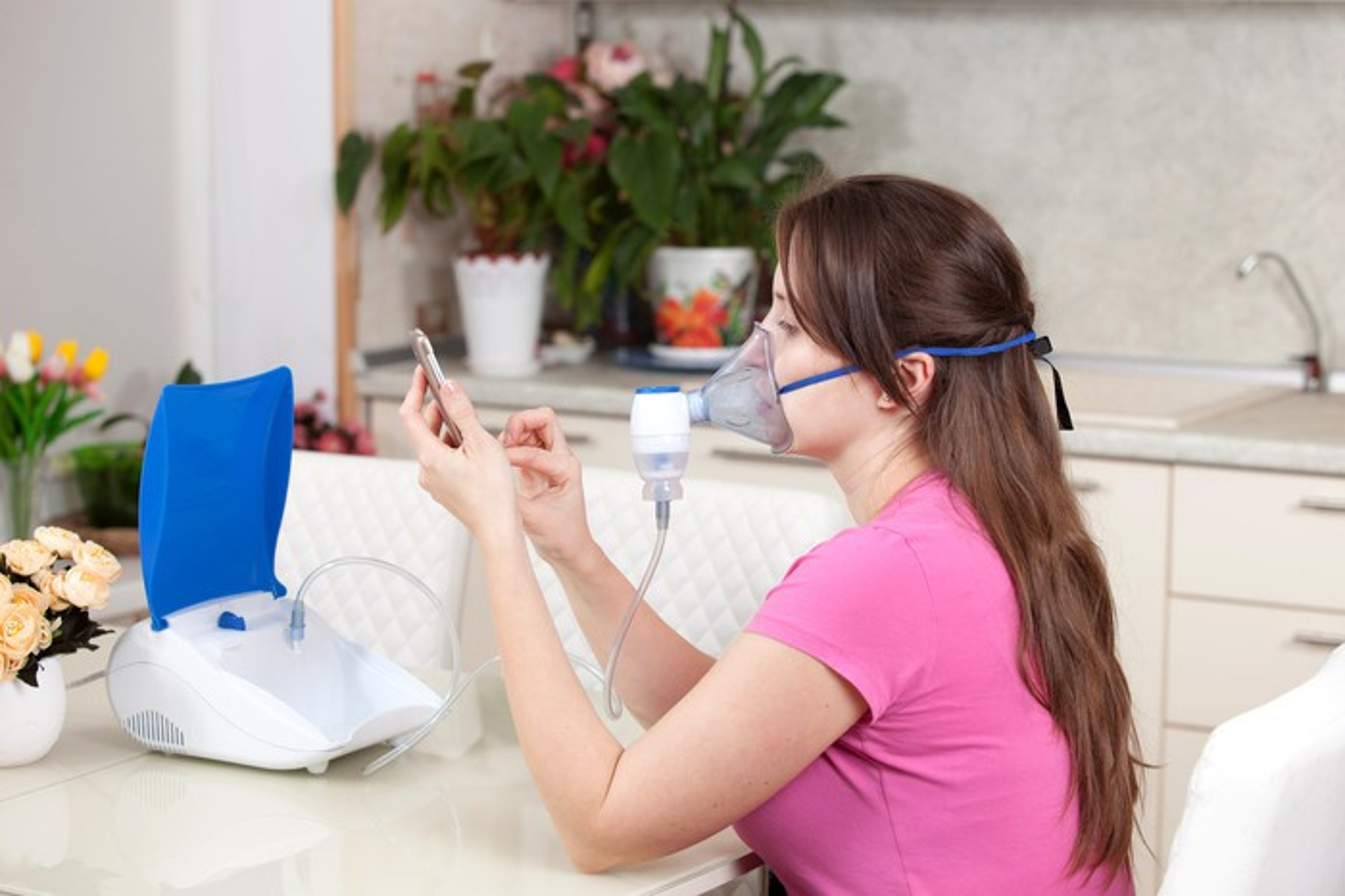 Woman using a nebulizer to inhale medicine.