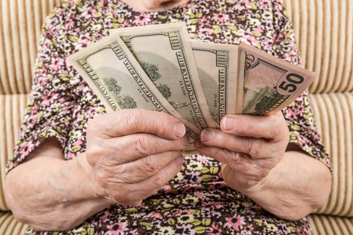 An elderly woman holding $100 and $50 bills.