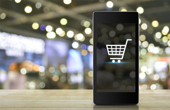 A smartphone balanced on its bottom edge, with a shopping cart icon on the screen.