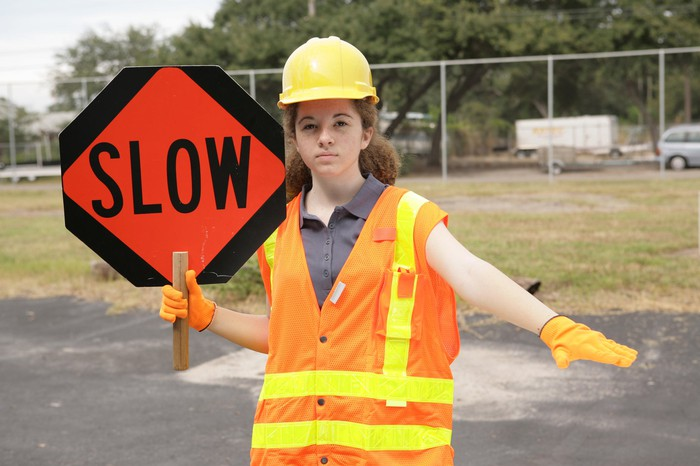 "A female traffic guard holding a sign that says ""SLOW"" and signaling with her hand to slow down"