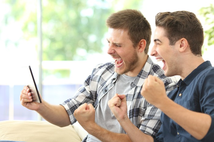 Two men excitedly streaming TV on a tablet