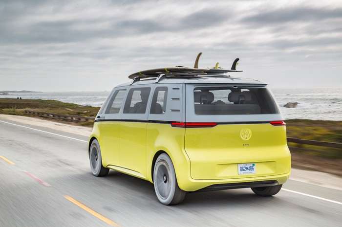 The yellow and white I.D. Buzz Concept, photographed from behind while driving on a coastal road.