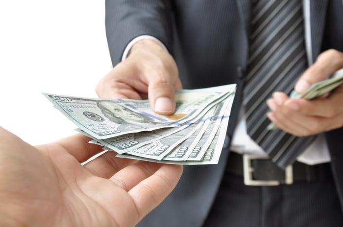 A man hands over multipe hundred dollar bills.