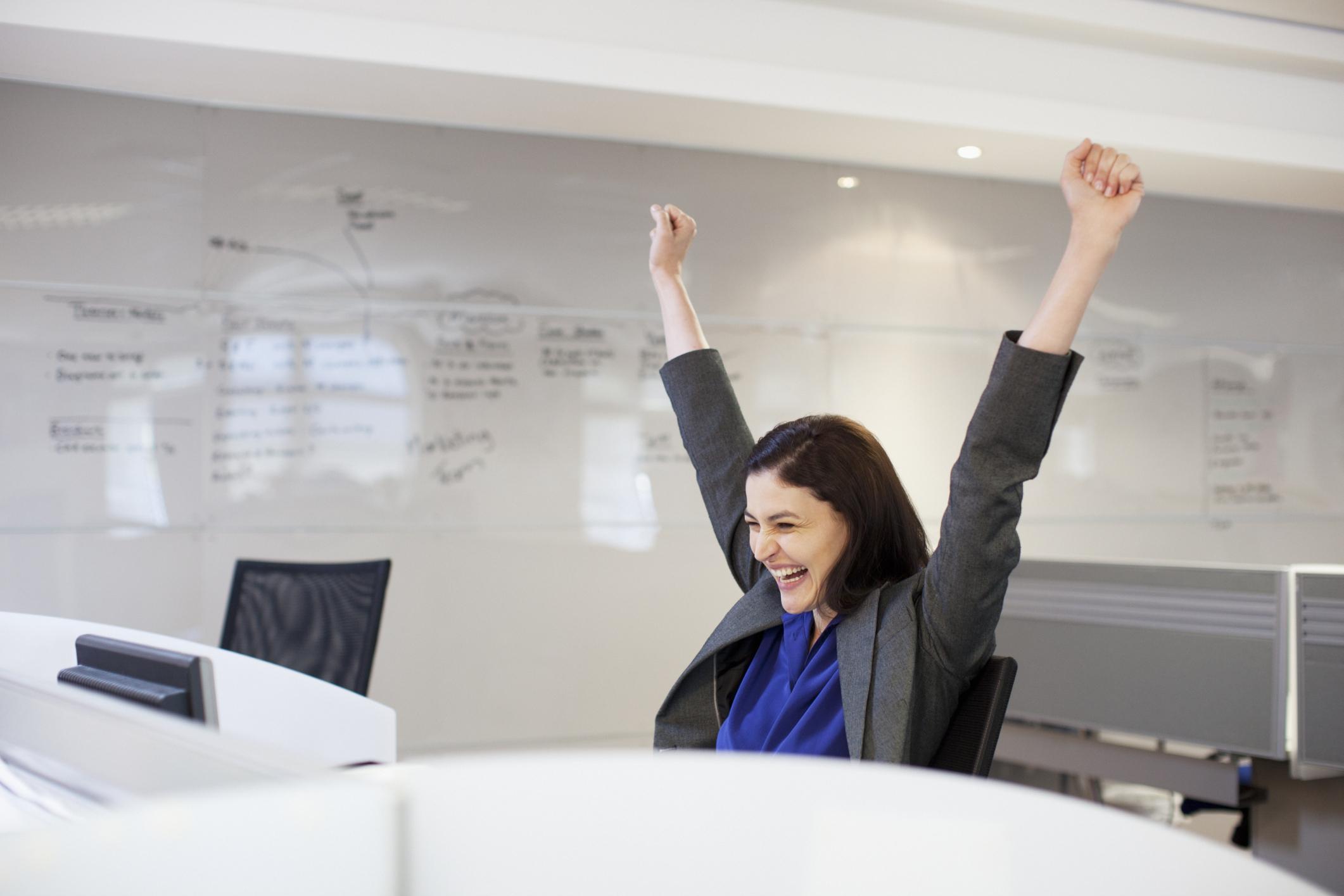 A woman raises her arms in triumph.