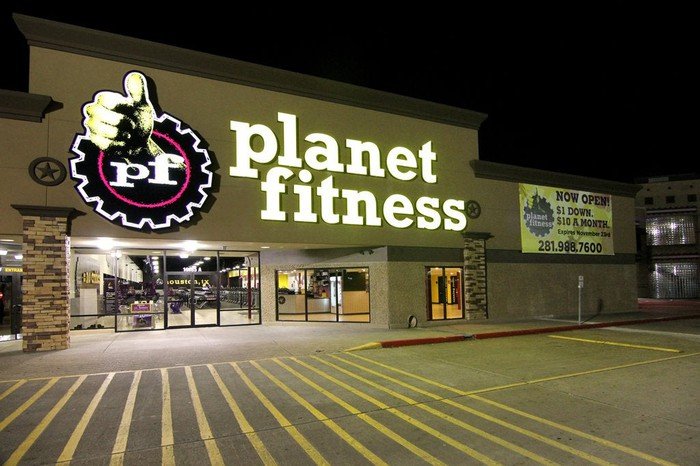 The exterior of a Planet Fitness store at night.