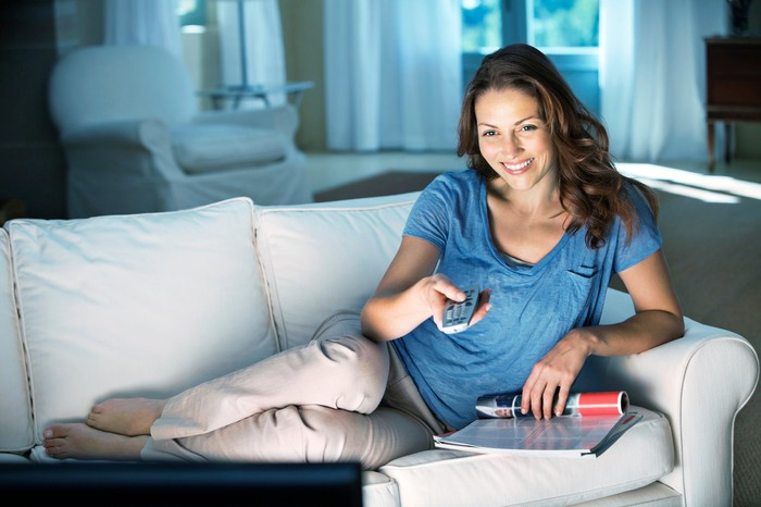 Smiling young woman watching TV on a white couch, remote in hand.