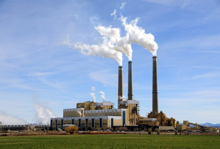 A coal power plant with smoke coming out of smokestacks.
