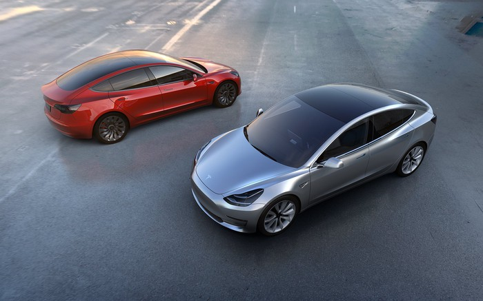 The all-new Tesla Model 3 in silver and red.